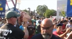 Ruben Israel and an associate carry a pig's head on a stick at the Dearborn Islamic festival.