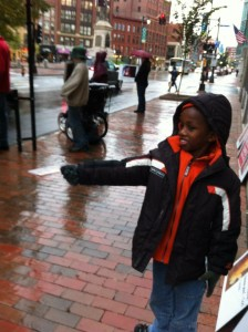 Hebert's adopted 8-year-old son from Ethiopia offers a passerby a tract.