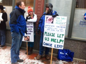 A man holds a pro-life sign to offer help to women during the protest.