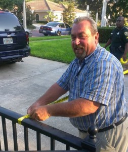 John Barros helps police tape off the abortion facility's driveway.