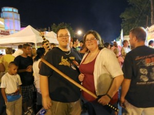 Festival-goers hold wooden swords sold by an event vendor.