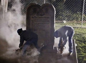 Workers remove the Oklahoma Ten Commandments monument by night.